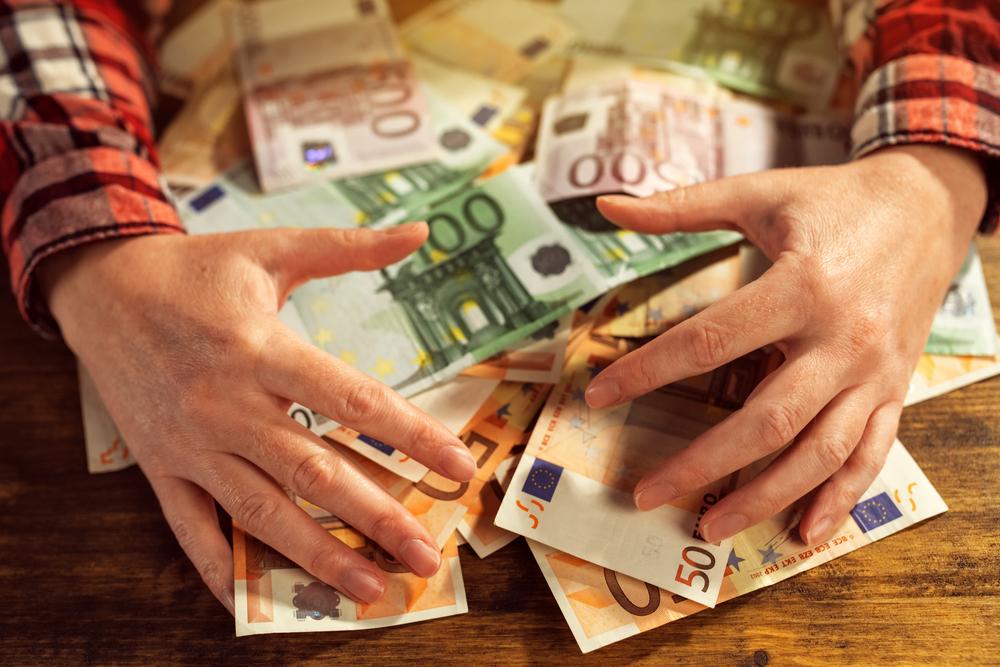 Mann greift auf einem Tisch nach Geldscheinen